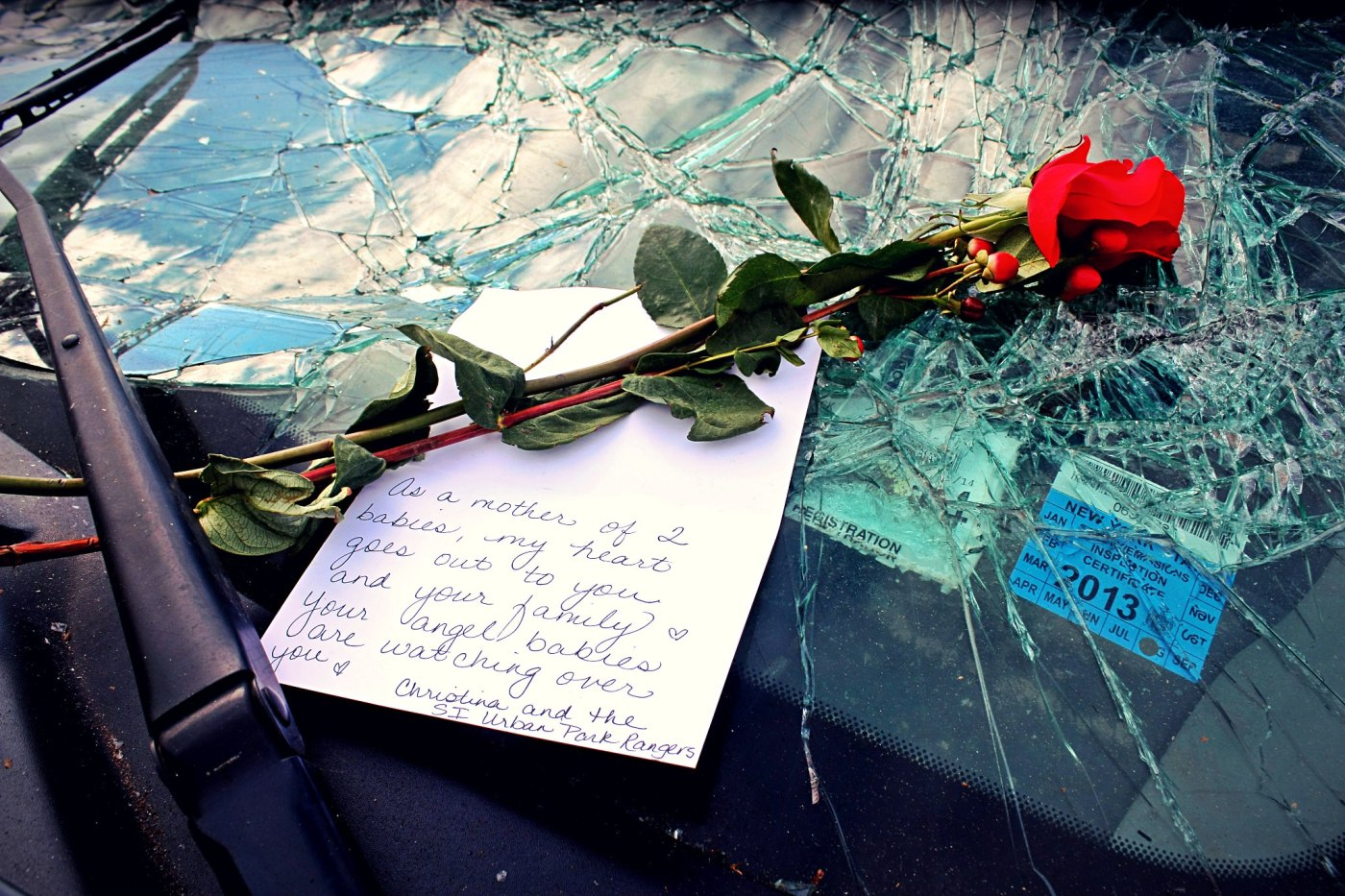 """November 3rd, 2012: A rose and a note left on a car in Staten Island that belonged to a woman who abandoned the car after it was overtaken by flood water during Hurricane Sandy. She had her two sons with her - 2 and 4 years old - and they were ripped from her arms by the rising water and drowned. The note says: """"As a mother of two babies, my heart goes out to you and your family. Your angle babies are watching over you. - Christina and the SI Urban Park Rangers"""""""