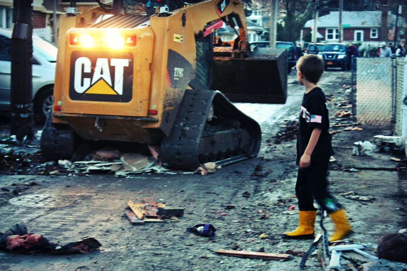 November 11th, 2012: A young boy looks on as a skid loader clears debris off of the road in New Dorp Beach, Staten Island.