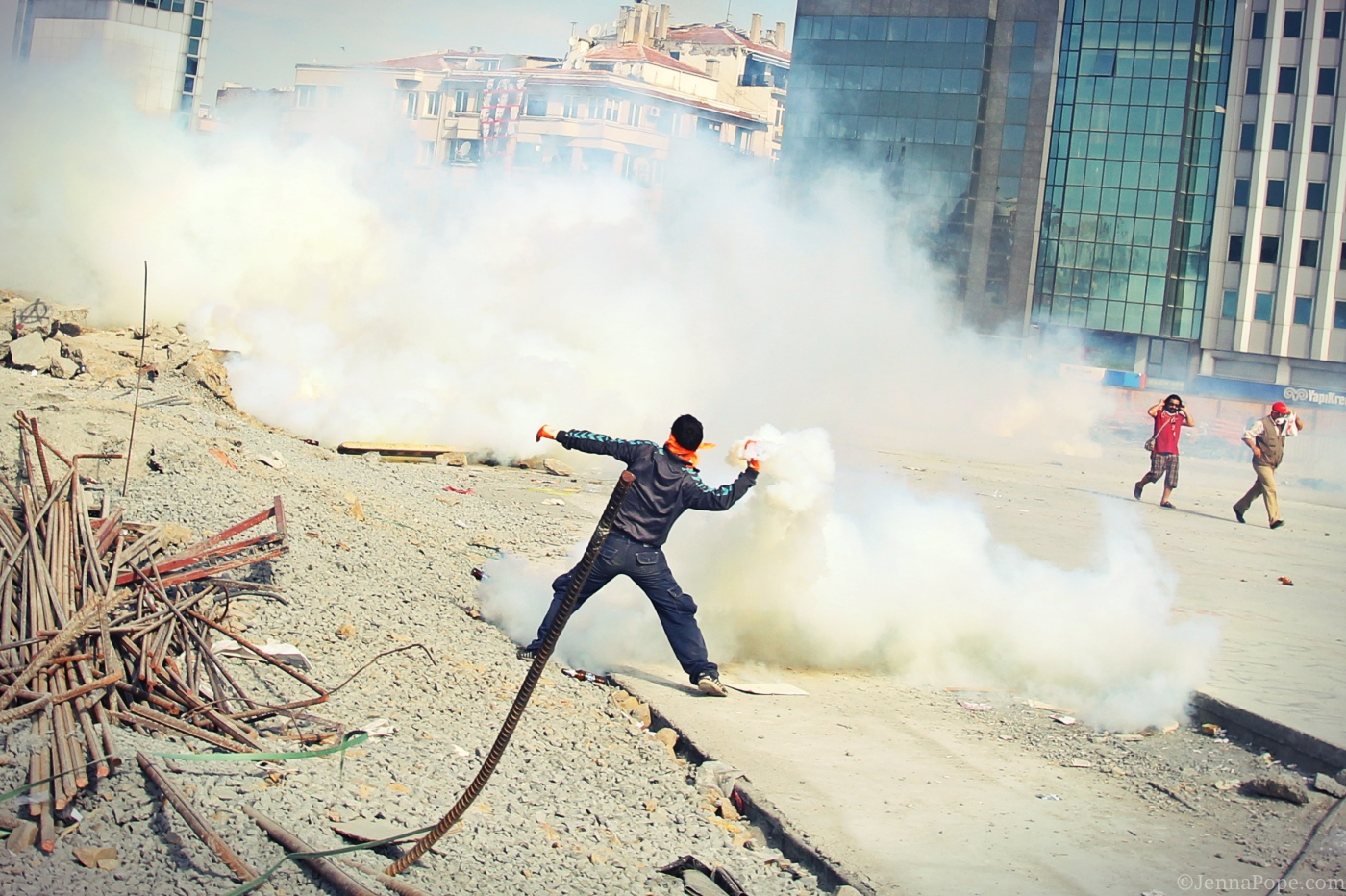 A protestor throws a tear gas canister back towards police.