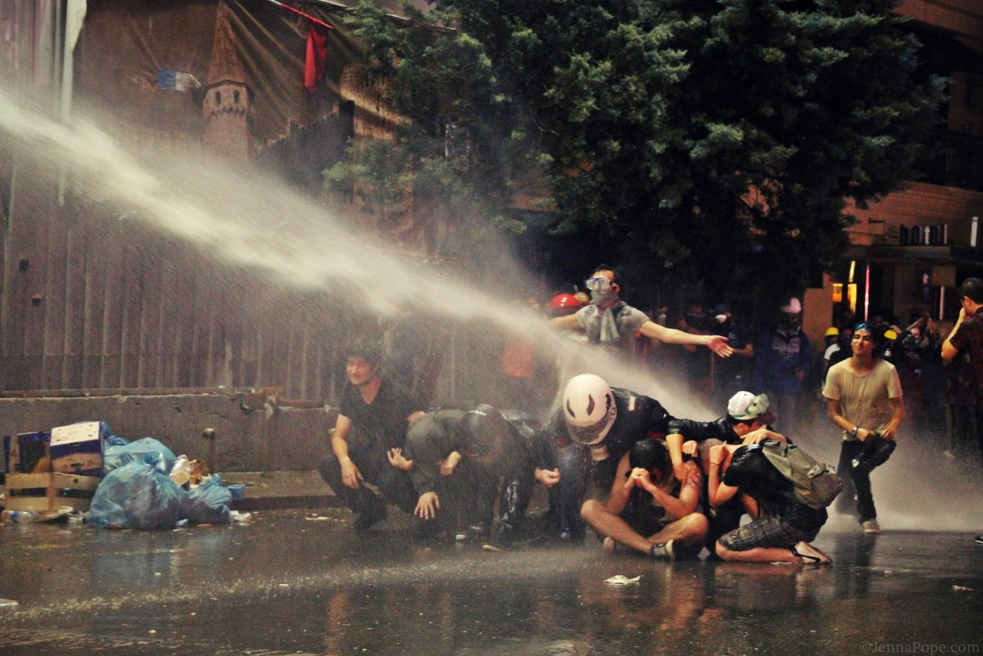 Protestors being sprayed with a water cannon.