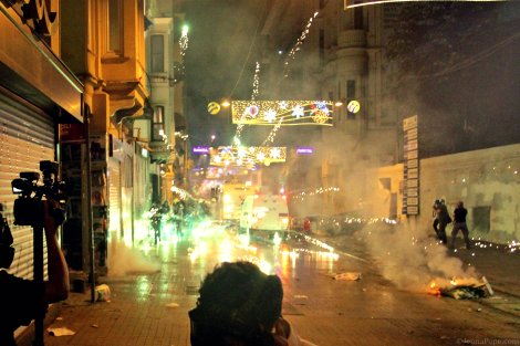 Protestors shooting fireworks at the police as the police shoot tear gas and water cannons at protestors.