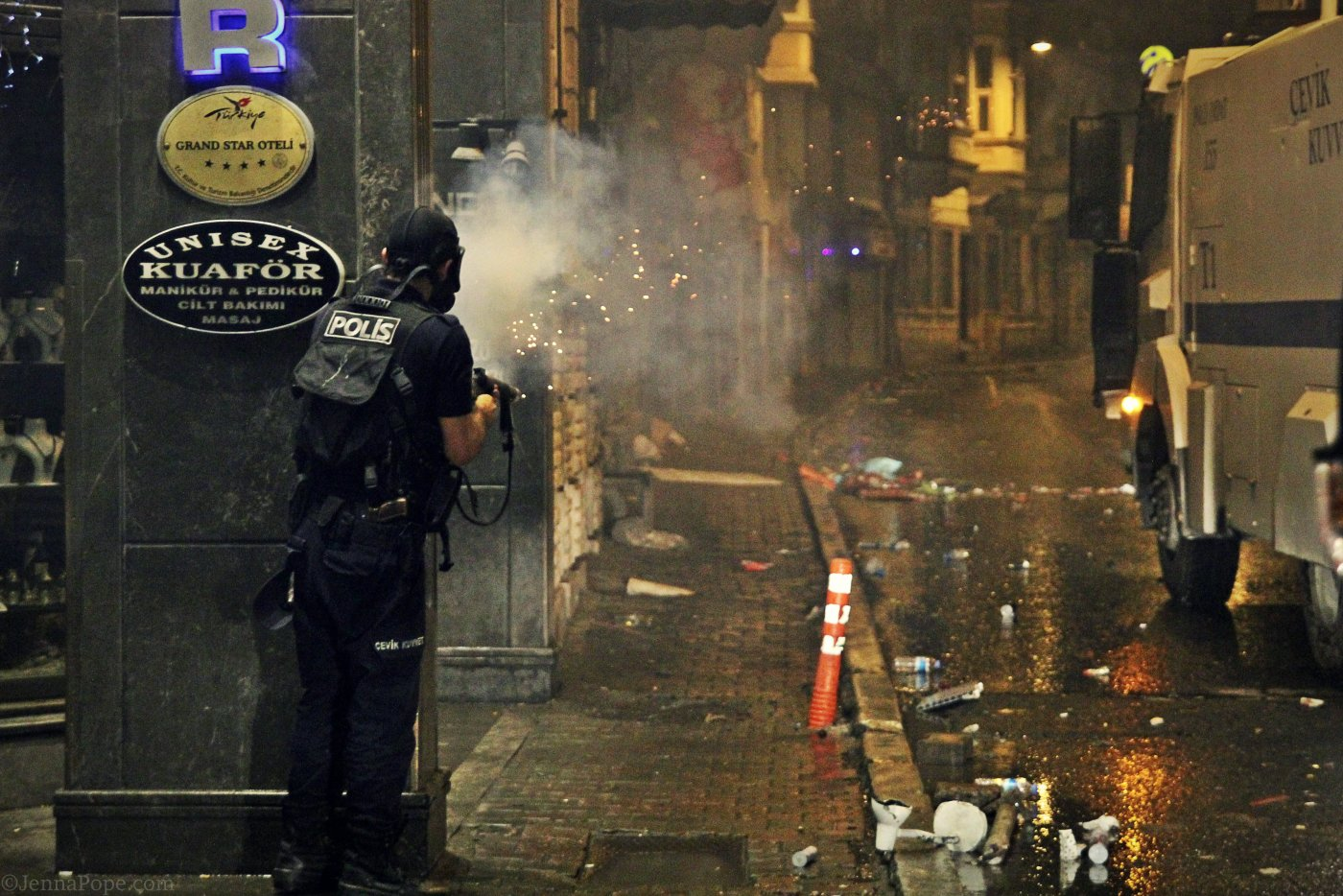 A police officer firing tear down the street towards protestors.
