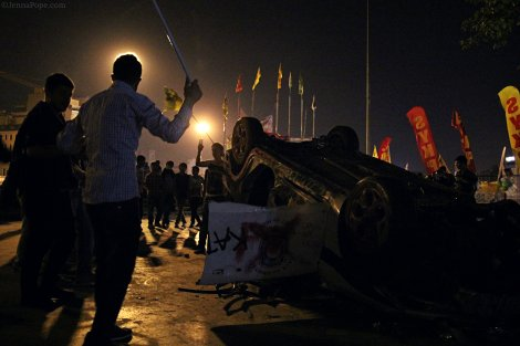 Protestors dancing around a destroyed police car at the entrance to Gezi Park.