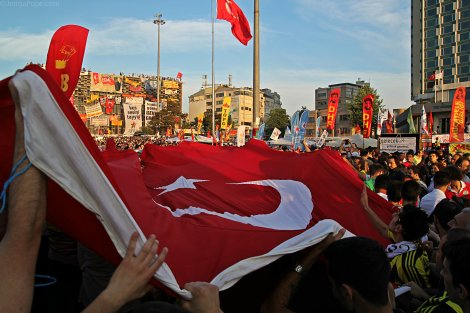 Protestors carry a large Turkish flag through Taksim Square.