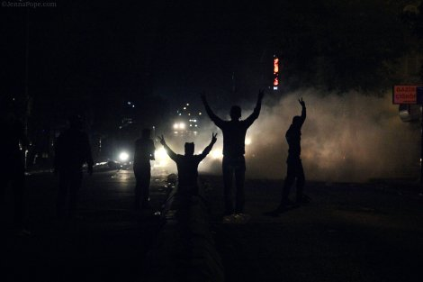 Protestors hold up peace signs as the headlights from two water cannon trucks shine on them.