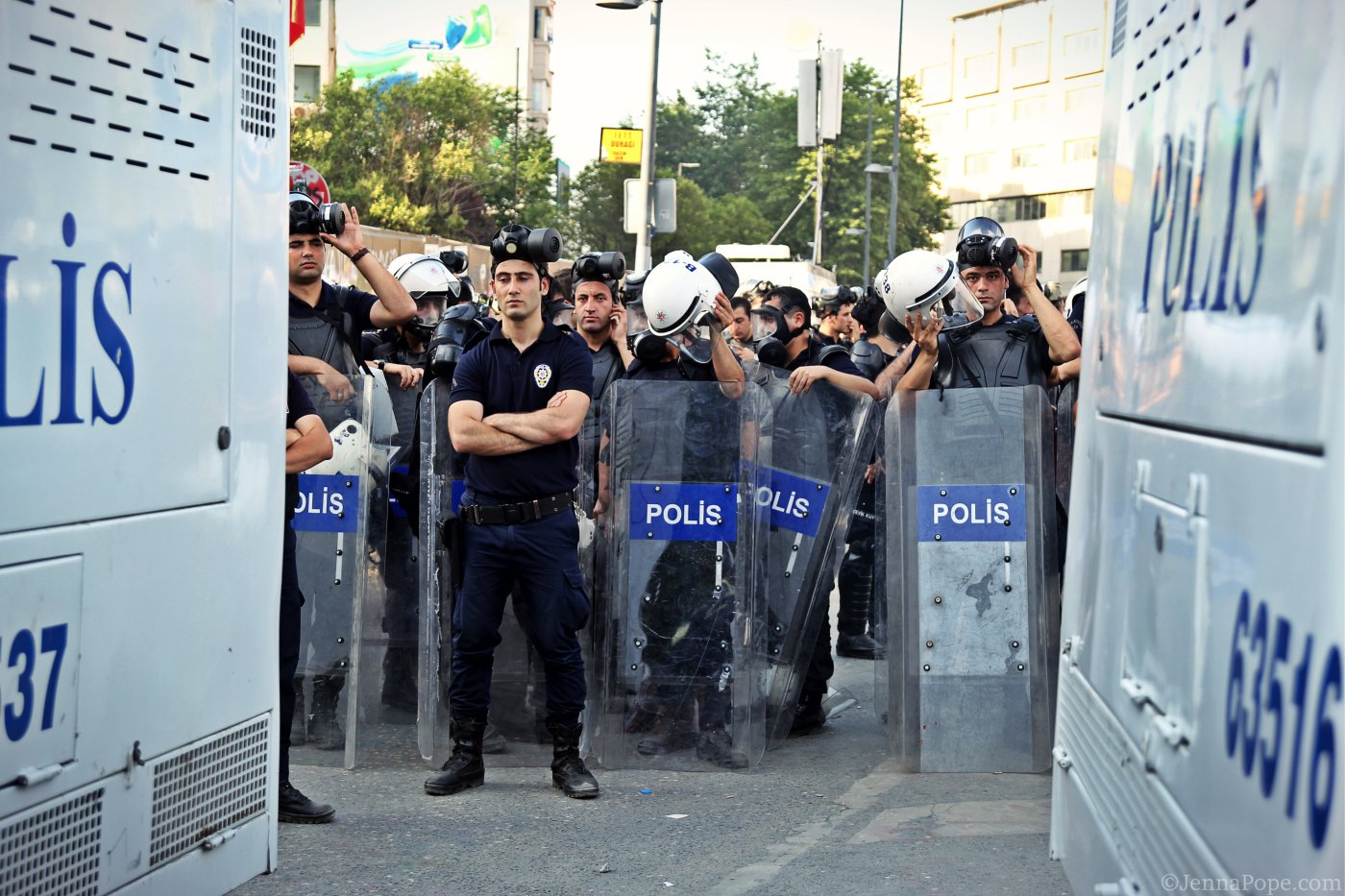 Police officers stand behind two water cannon trucks in Taksim Square.